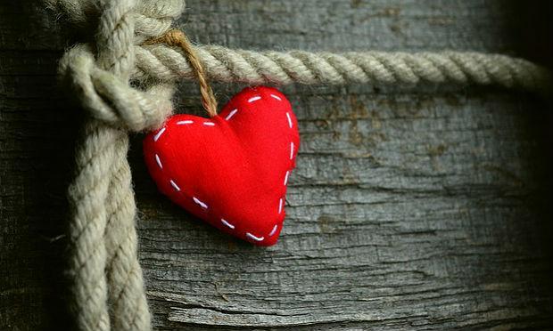 Imagem de coração vermelho de tecido com pontilhado branco amarrado a corda