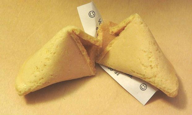 Imagem de biscoito da sorte com papel com mensagem embaixo (Foto: Pixabay)